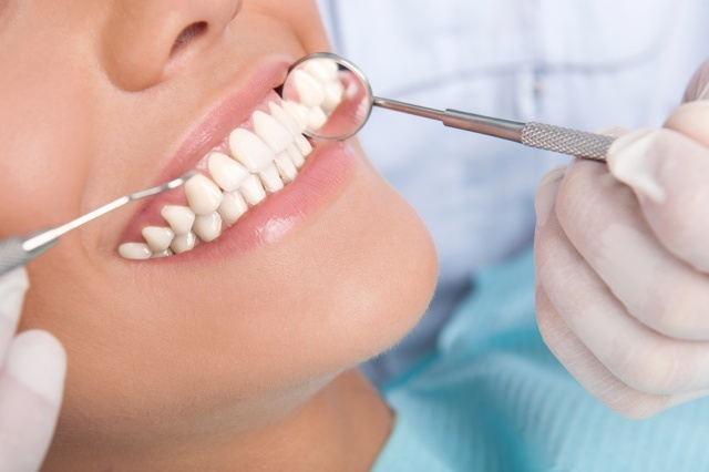 Patient at dentist office. Close-up of young woman sitting at the chair in dental office and smiling while doctor examining her teeth